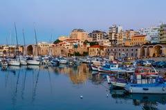伊拉克利翁老港口有渔船和小游艇船坞的在微明期间,克利特,希腊 库存图片