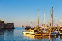 伊拉克利翁老港口有渔船和小游艇船坞的在微明期间,克利特,希腊 免版税库存照片