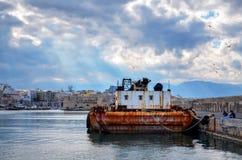 伊拉克利翁,克利特-希腊 在伊拉克利翁港的浮动起重机  堡垒Koules和一部分的背景的伊拉克利翁 太阳r 库存图片