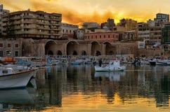 伊拉克利翁,克利特/希腊 在旧港口的日落与威尼斯式造船厂在伊拉克利翁 有他的渔夫 库存图片