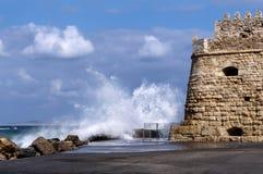 伊拉克利翁,克利特-希腊 海挥动击中防堤在堡垒Koules旁边在伊拉克利翁市旧港口  晴朗 免版税库存照片