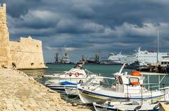 伊拉克利翁,希腊- 2017年11月:五颜六色的渔船临近老威尼斯式堡垒Koule,伊拉克利翁口岸,克利特 免版税库存图片