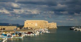 伊拉克利翁,希腊- 2017年11月:五颜六色的渔船临近老威尼斯式堡垒Koule,伊拉克利翁口岸,克利特 免版税库存照片
