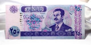 伊拉克的钞票白色缎背景的 免版税库存图片