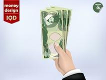 伊拉克第纳尔在手边金钱纸,伊拉克金钱在手边兑现 免版税库存照片