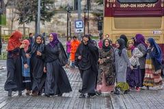 伊斯兰教的衣裳的土耳其女小学生在街道上 图库摄影