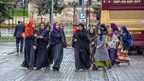 伊斯兰教的衣裳的土耳其女小学生在街道上 免版税图库摄影