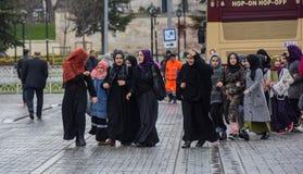 伊斯兰教的衣裳的土耳其女小学生在街道上 库存图片