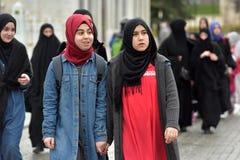 伊斯兰教的衣裳的土耳其女小学生在街道上 免版税库存图片