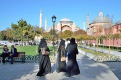 伊斯坦布尔,土耳其, 2013年10月, 18日 传统伊斯兰教的衣物的妇女走在Aya Sofya附近的 免版税库存照片