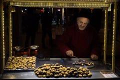 伊斯坦布尔,土耳其- 2015年12月28日:一位老栗子卖主的图片在Istiklal街道上的一个冷的冬天晚上 免版税图库摄影