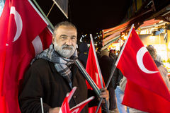 伊斯坦布尔,土耳其- 2015年12月30日:卖在伊斯坦布尔的欧洲部分的老人土耳其旗子 免版税库存照片