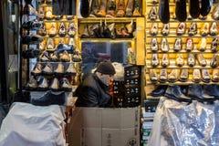 伊斯坦布尔,土耳其- 2015年12月30日:在休息在他的商店的香料义卖市场附近穿上鞋子卖主 图库摄影