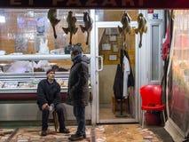 伊斯坦布尔,土耳其- 2015年12月30日:宰割谈论与在他的商店前面的一个客户在城市的欧洲边在Th 库存图片