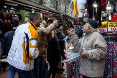 伊斯坦布尔,土耳其- 2015年12月28日:老商人设法卖反重音头按摩设备对笑的人在香料附近 免版税库存照片