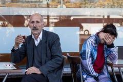 伊斯坦布尔,土耳其- 2015年12月28日:老在一个咖啡馆的大阳台的人饮用的茶在城市的亚洲边的 免版税库存图片