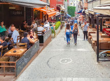 伊斯坦布尔,土耳其- 2017年6月02日:走在一条狭窄的街道的人们用酒吧填装了在Kadikoy,伊斯坦布尔 免版税库存图片