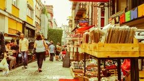 伊斯坦布尔,土耳其- 2017年6月02日:走在狭窄的街道的人们用老商店填装了在Kadikoy,伊斯坦布尔 免版税库存图片