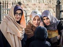 伊斯坦布尔,土耳其- 2015年12月27日:头戴伊斯兰教的头巾的土耳其少妇listenning对在小组的一个智能手机 免版税库存图片