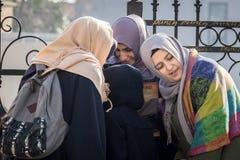 伊斯坦布尔,土耳其- 2015年12月27日:头戴伊斯兰教的头巾的土耳其少妇listenning对在小组的一个智能手机 库存图片