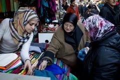 伊斯坦布尔,土耳其- 2015年12月28日:头戴伊斯兰教的头巾的小组妇女谈判穿衣在bazzar的一位织品客商 图库摄影