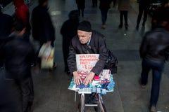 伊斯坦布尔,土耳其- 2015年12月29日:组织他的商品的瞎的卖主,当步行者通过与速度迷离时 免版税图库摄影