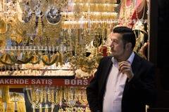 伊斯坦布尔,土耳其- 2015年12月30日:Gran义卖市场饮用的茶的珠宝商在他的商店前面 免版税库存照片
