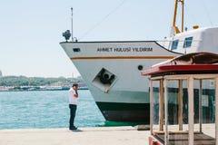 伊斯坦布尔, 2017年6月17日:一个人在海滩的电话谈话在一艘大客船旁边 免版税库存图片