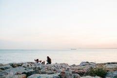 伊斯坦布尔, 2017年6月14日:两个朋友坐海岸在海附近,传达并且享受Bosphorus的看法和 库存图片