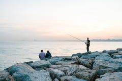 伊斯坦布尔, 2017年6月14日:两个朋友坐海岸在海附近,传达并且享受Bosphorus的看法和 免版税库存照片
