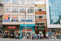 伊斯坦布尔, 2017年6月14日:人人群步行沿着向下在大厦背景的街道与全部的商店和咖啡馆 免版税图库摄影
