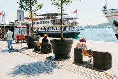 伊斯坦布尔, 2017年6月17日:人们坐长凳和基于Bosphorus的岸 附近的轮渡和乘客 免版税库存照片