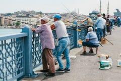 伊斯坦布尔, 2017年6月17日:传统土耳其渔爱好 许多人民在加拉塔桥梁钓鱼 普通的寿命 免版税库存图片
