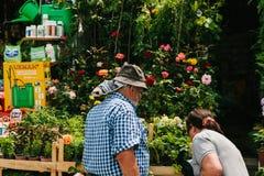 伊斯坦布尔, 2017年6月15日:地道场面 一位地方花卖主提供买家买美丽的鲜花 图滑稽的从事园艺的现有量拿着其金属准备好的铁锹小 免版税库存照片