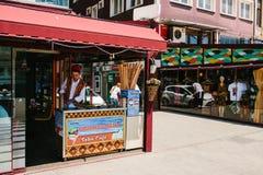 伊斯坦布尔, 2017年6月15日:地道场面 全国衣裳的一位街道冰淇凌卖主 街道咖啡馆 库存图片