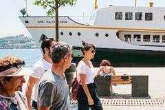 伊斯坦布尔, 2017年6月17日:女孩坐一条长凳和基于长凳在一艘大客船旁边 另外人员 免版税图库摄影