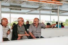 伊斯坦布尔, 2017年6月17日:当地人民的三个成年男性朋友乘轮渡或客船游泳,沟通并且笑 库存照片