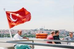伊斯坦布尔, 2017年6月17日:当地居民在水移动乘轮渡或客船 一个人在土耳其旗子旁边坐 免版税库存照片