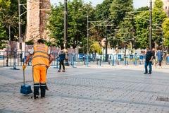 伊斯坦布尔, 2017年6月15日:清扫在街道上的明亮的橙色制服的管理员瓦片在Sultanahmet区 免版税库存图片