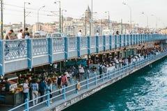 伊斯坦布尔, 2017年6月15日:走在加拉塔桥梁的人们 与顾客的咖啡馆在桥梁下 免版税库存照片