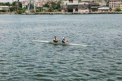 伊斯坦布尔, 2017年6月17日:运动员一个男人和一名妇女皮船的在Bosphorus漂浮 配合或准备为 免版税图库摄影