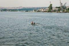 伊斯坦布尔, 2017年6月17日:运动员一个男人和一名妇女皮船的在Bosphorus漂浮 配合或准备为 库存图片