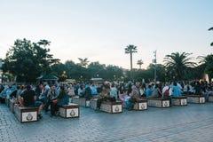 伊斯坦布尔, 2017年6月16日:伊斯兰教的宗教的许多人民在蓝色清真寺旁边采取在Sultanahmet广场的食物 库存照片