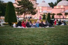 伊斯坦布尔, 2017年6月16日:伊斯兰教的宗教的许多人民在蓝色清真寺旁边采取在Sultanahmet广场的食物 库存图片