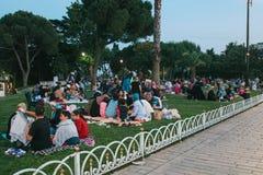 伊斯坦布尔, 2017年6月16日:伊斯兰教的宗教的许多人民在蓝色清真寺旁边采取在Sultanahmet广场的食物 免版税库存图片