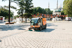 伊斯坦布尔, 2017年6月16日:使用清洁机器的街道管理员清扫和清洗边路瓦片 免版税图库摄影