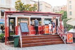 伊斯坦布尔, 2017年6月15日:受欢迎在游人和当地人民中是咖啡馆以在正方形的一辆电车的形式在旁边 免版税库存照片