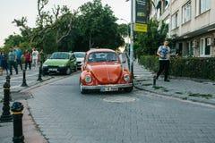 伊斯坦布尔, 2017年6月14日:有两个人的红色汽车在街道上在Moda邻里在伊斯坦布尔,土耳其 免版税图库摄影