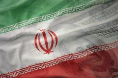 伊朗的五颜六色的挥动的国旗美国美元金钱背景的 免版税库存图片