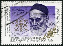伊朗- 1989年:展示回教什叶派领袖霍梅尼1902-1989,口号 免版税库存照片